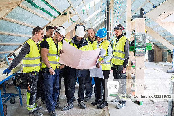 Manager standing with manual workers while reading blue prints at construction site