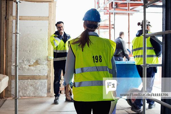 Handwerker diskutieren im Stehen auf der Baustelle