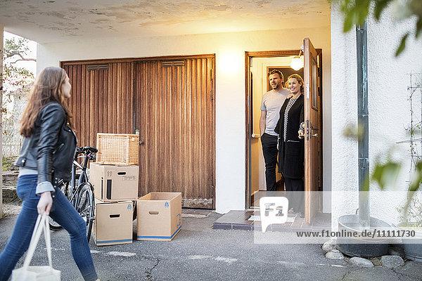 Eltern  die ihre Tochter beim Spaziergang mit Kartonagen und Fahrrad vor dem neuen Haus betrachten