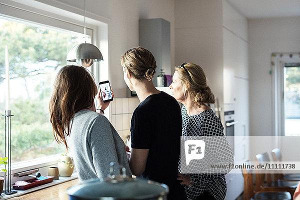 Frau nimmt Selfie  während sie mit der Familie in der Küche im neuen Zuhause steht