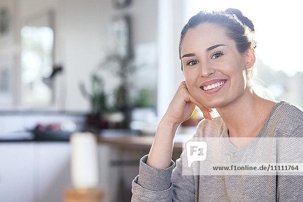 Porträt einer glücklichen Frau  die in der Küche des neuen Hauses sitzt.