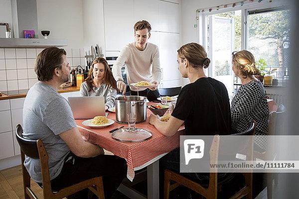 Mann serviert Essen für die Familie am Esstisch