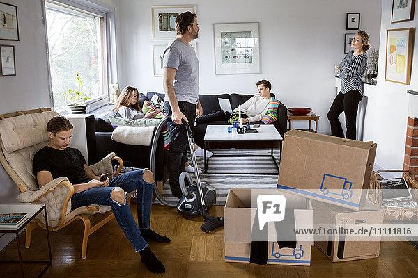 Eltern arbeiten  während die Geschwister im Wohnzimmer des neuen Hauses sitzen.