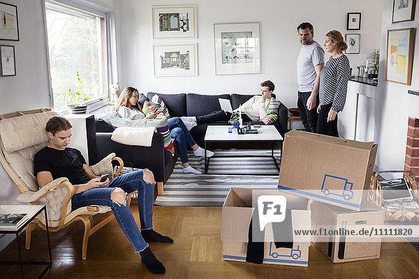 Eltern  die Geschwister im Wohnzimmer mit Pappkartons anschauen