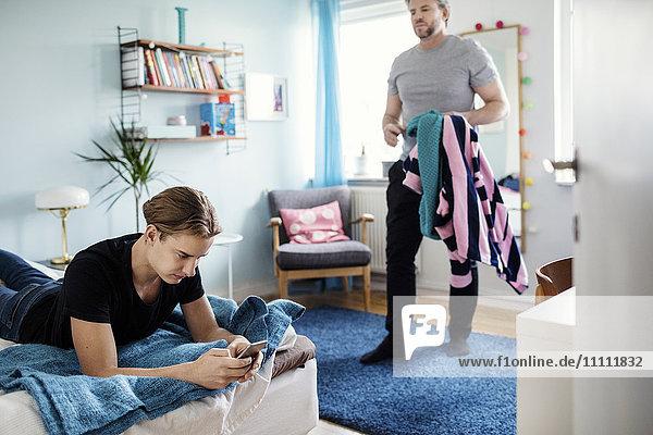 Wütender Mann  der Kleidung hält  während er den Sohn mit einem Smartphone im Bett im neuen Zuhause ansieht.