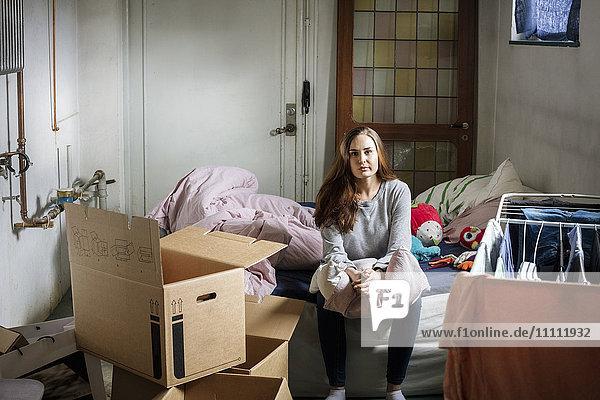 Porträt einer jungen Frau auf dem Bett im neuen Zuhause