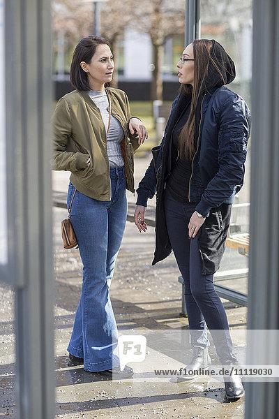 Women talking on bus stop