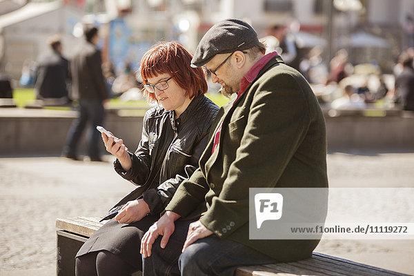 Schweden  Sodermanland  Frau mit Down-Syndrom sitzt auf der Bank und überprüft zusammen mit ihrem Freund Smartphone