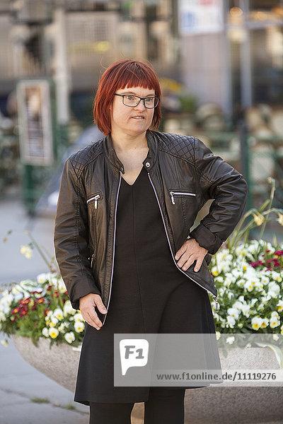 Sweden  Sodermanland  Stockholm  Sodermalm  Medborgarplatsen  Portrait of woman with down syndrome against flowerbed