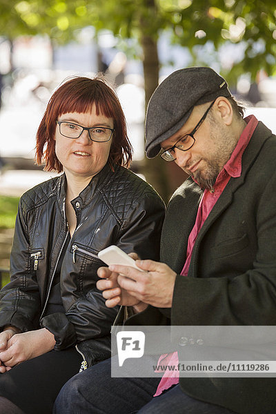 Sweden  Sodermanland  Woman with down syndrome sitting next to boyfriend checking smart phone