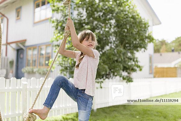 Schweden  Gotaland  Bohuslan  Grebbestad  Girl (6-7) Kletterseil im Hinterhof
