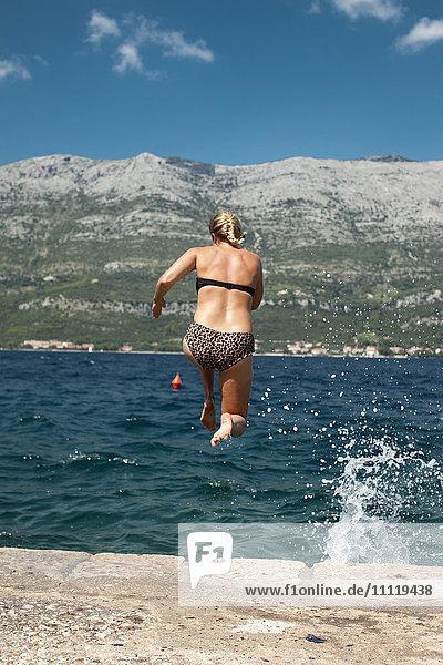 Kroatien  Korcula  Blonde Frau im Bikini springt vom Steinpier ins Wasser