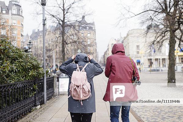 Schweden  Stockholm  Junges Paar bei Schneefall durch die Stadt laufen