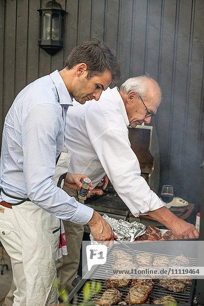 Schweden,  Zwei Männer grillen Fleisch