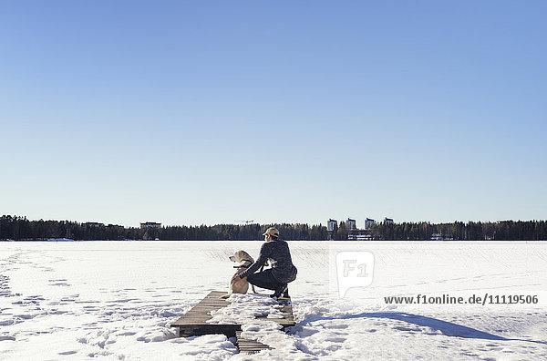 Schweden  Vasterbotten  Umea  Mann mit Hund mit Blick auf Winterlandschaft