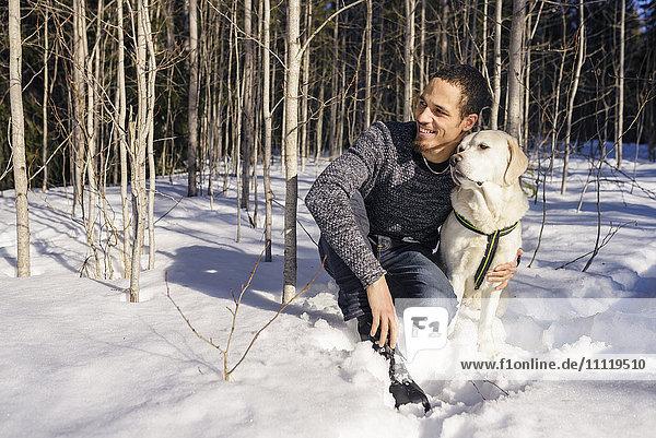 Schweden  Vasterbotten  Umea  Mann kniend mit Hund im Schnee