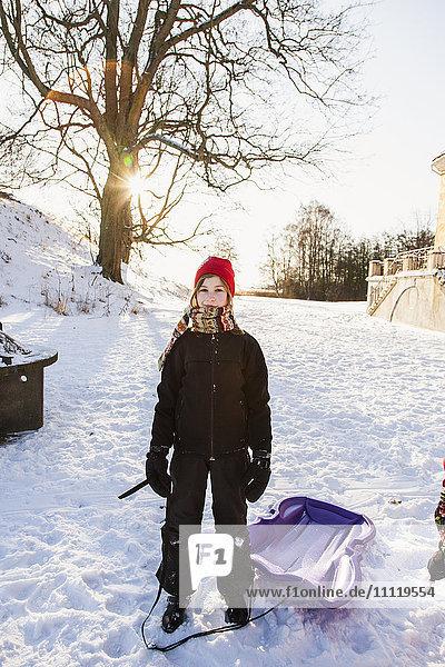 Schweden  Blekinge  Solvesborg  Mädchenporträt (12-13) mit Plastikschlitten