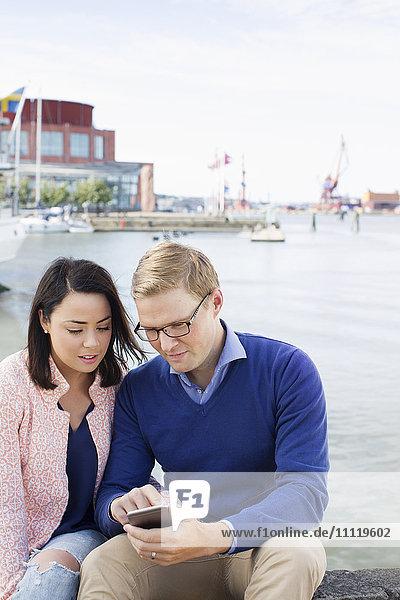 Schweden  Vastergotland  Göteborg  Junges Paar sitzt am Hafen und überprüft Smartphone