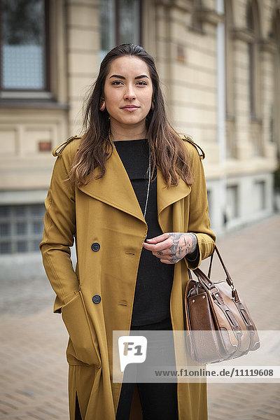Sweden  Skane  Kirstianstad  Portrait of young woman in yellow coat