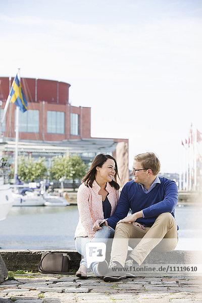 Schweden  Vastergotland  Göteborg  Lächelndes junges Paar auf der Promenade am Hafen sitzend und unterhaltend