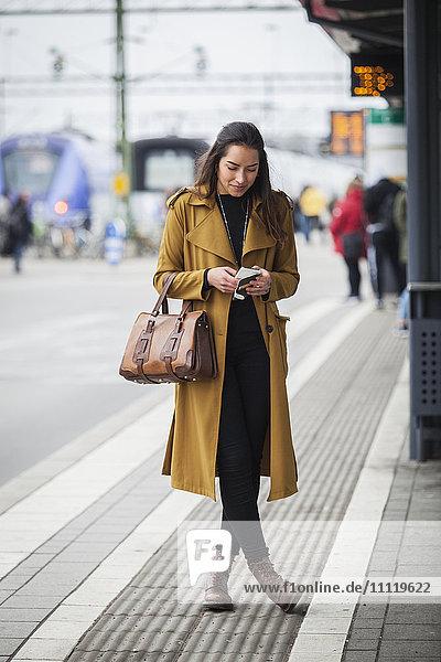 Schweden  Skane  Kirstianstad  Junge Frau beim Blick auf Smartphone am Bahnhof