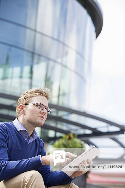 Schweden  Vastergotland  Göteborg  Junger Mann sitzend gegen Glasbau und mit digitaler Tafel