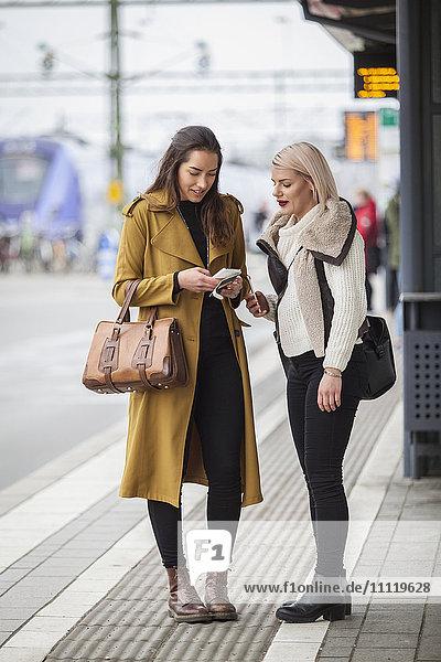 Schweden  Skane  Kirstianstad  Zwei junge Frauen stehen mit Smartphones am Bahnhof