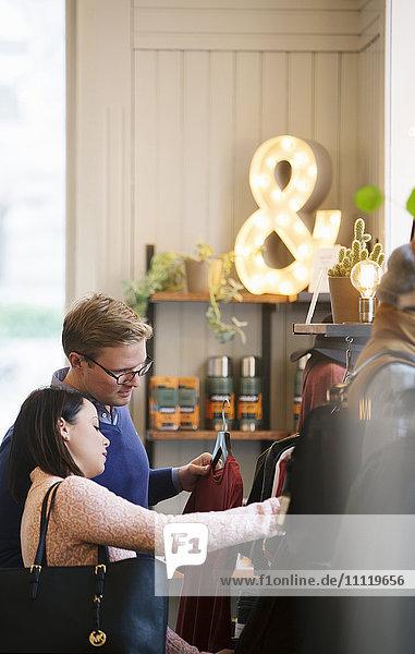 Schweden  Vastergotland  Junges Paar bei der Kleiderwahl im Geschäft