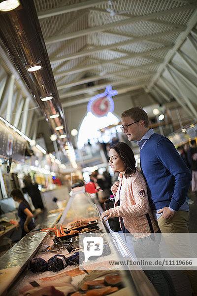 Schweden  Vastergotland  Göteborg  Junges Paar beim Kauf von Meeresfrüchten auf dem Markt