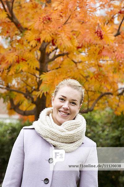 Schweden  Junge Frau im Mantel gegen den Herbstbaum