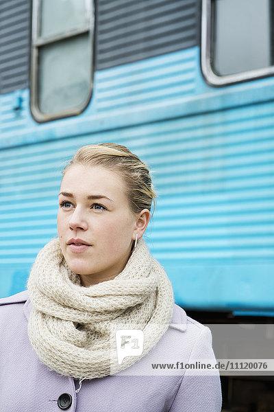 Schweden  Vastra Gotaland  Göteborg  Junge Frau im Mantel mit Zug im Hintergrund