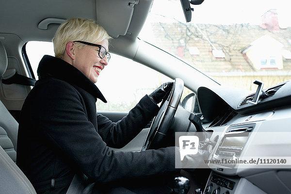 Schweden  Sodermanland  Stockholm  Blonde Frau auf driver´s Sitz Startauto