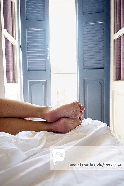 Griechenland  Kalymnos  Weibliche Beine auf Bett im sonnigen Schlafzimmer Griechenland, Kalymnos, Weibliche Beine auf Bett im sonnigen Schlafzimmer