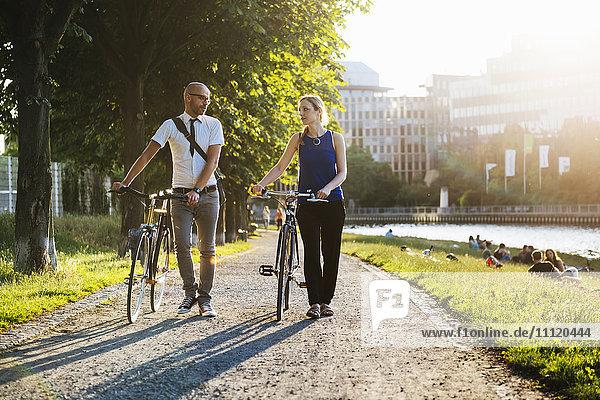Deutschland  Berlin  Mann und Frau zu Fuß mit dem Fahrrad in der Stadt
