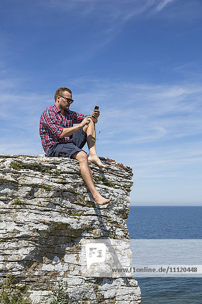 Sweden  Gotland  Mature man sitting on cliff at seashore and using telephone