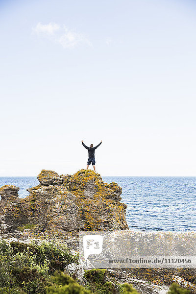 Sweden  Gotland  Mature man standing on rock at seashore with arms raised