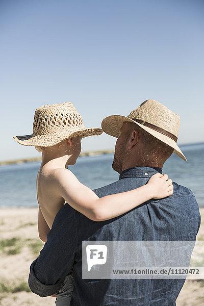 Sweden  Gotland  Mature man holding boy (8-9) at seashore