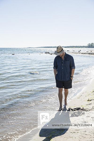Sweden  Gotland  Mature man walking along seashore