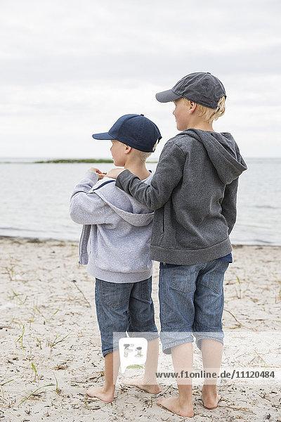 Sweden  Gotland  Boys (6-7  8-9) in baseball caps standing at beach
