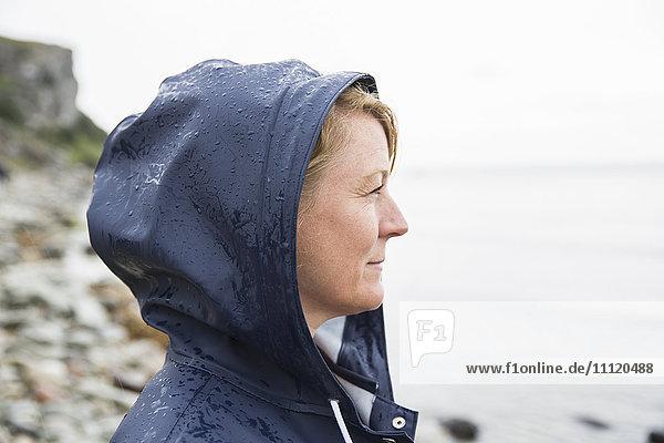 Sweden  Gotland  Mature woman in hood at beach