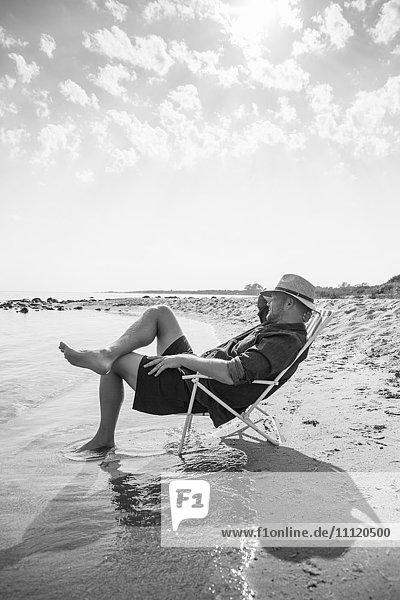 Sweden  Gotland  Mature man sitting on deckchair at seashore
