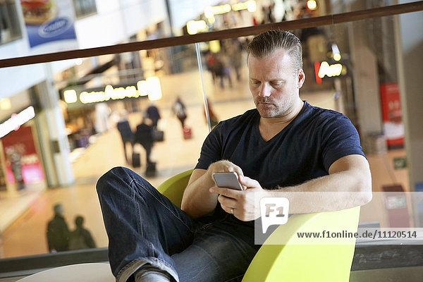 Germany  Hamburg  Mature man sitting in airport hall and using telephone