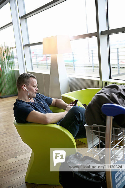 Germany  Hamburg  Mature man sitting at airport hall and using telephone