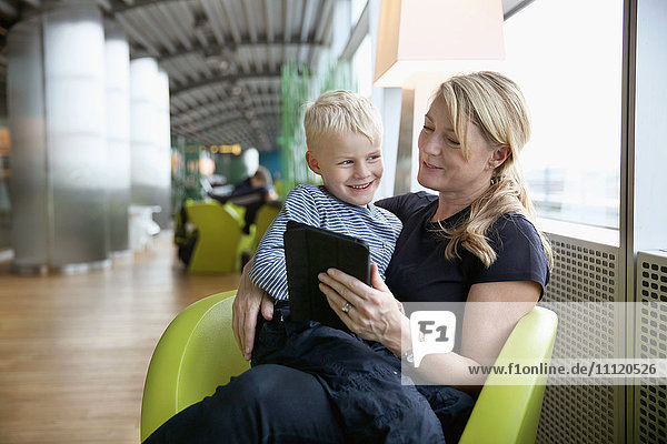 Germany  Hamburg  Mature woman sitting at airport hall and using tablet with boy (6-7) sitting on her lap