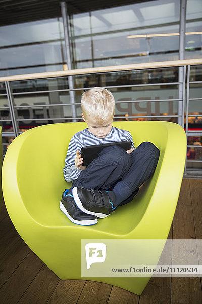 Germany  Hamburg  Boy (6-7) sitting at airport hall and using tablet