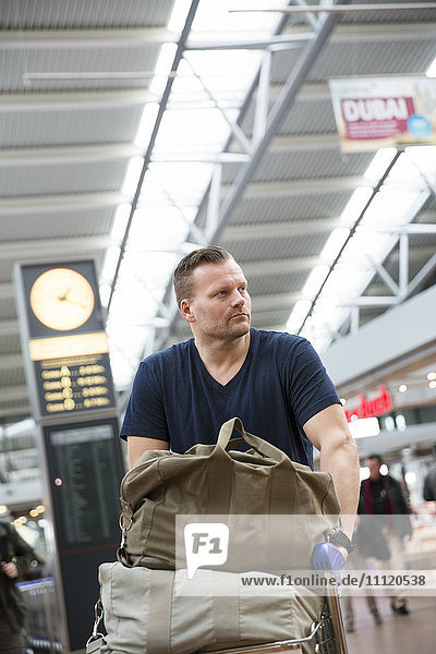 Germany  Hamburg  Mature man with luggage trolley at airport