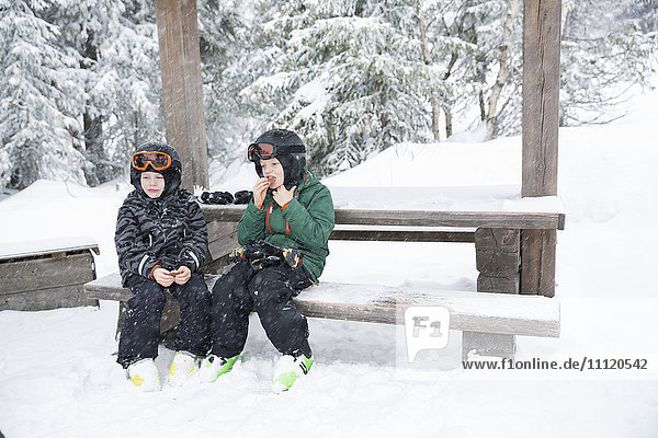 Sweden  Dalarna  Salen  Boys (6-7  8-9) wearing helmets and goggles sitting on bench surrounded by winter landscape