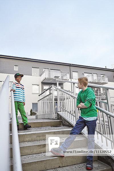 Schweden  Vastra Gotaland  Grimmered  Jungen (8-9) auf der Treppe stehend und sprechend