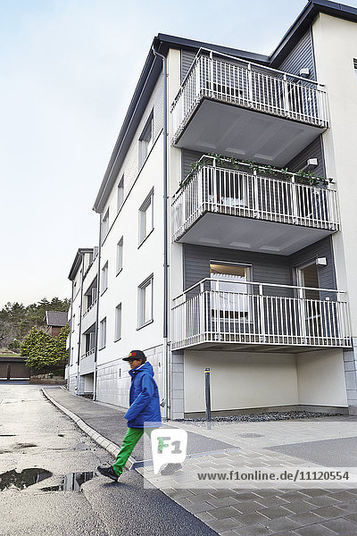 Schweden  Vastra Gotaland  Grimmered  Boy (8-9) überquert Straße neben Wohnhaus