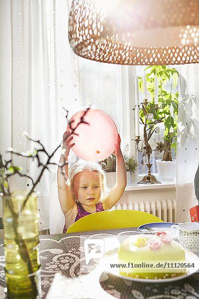 Schweden  Mädchen (2-3) steht am Tisch und hält den Ballon.